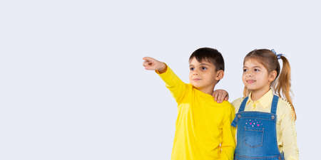 Banner. Cute kids on a white background. The boy shows something in the distance, the girl stands nearby and smiles. High quality photo