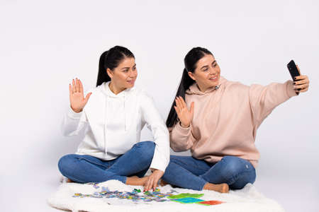 Twins are sitting on the floor, putting together a puzzle and communicating via video communication on a smartphone. White background.