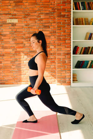 Active sportive woman doing fitness exercises with dumbbells against the background of a brick wall.
