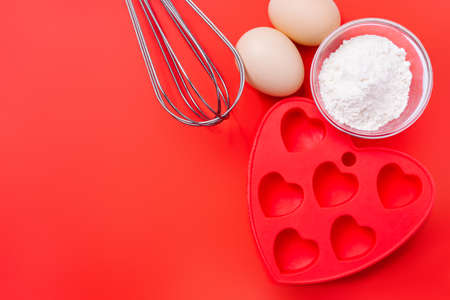 Whisk, red silicone mold and ingredients for a dessert on a festive table on Valentines Day.