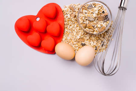 Muesli, whisk and baking dish, making delicious Valentines Day surprise on ultimate gray background.