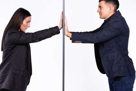 Business partners pushing a wall at each other on a white background.