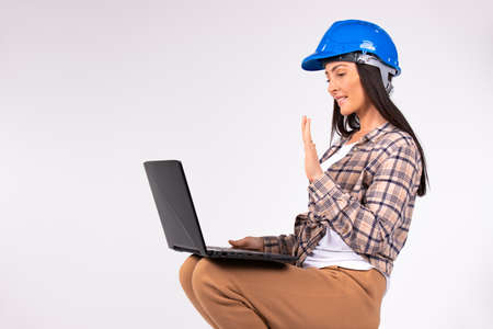 New norms and online concept. Woman in hard hat greeted by video communication while holding laptop on her feet. White background.