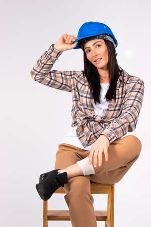 Attractive brunette woman posing in blue hard hat while sitting on a chair. White background.