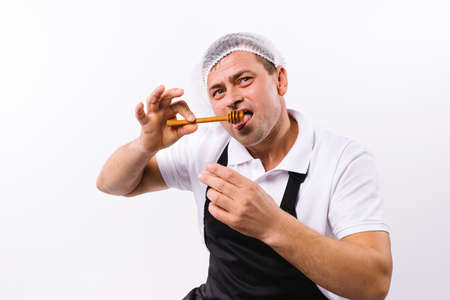 A chef in a black apron with a bowl tastes fragrant sweet honey on a white background.
