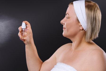 Profile photo. Senior woman with a bandage on her head sprays facial spray on a black background. Фото со стока