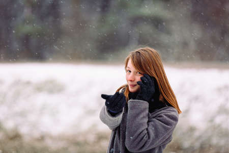 A cute girl of caucasian appearance is talking on the phone and looking at the camera on a snowy background.
