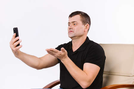 Caucasian surdomute man communicates non-verbal via video call by stretching out his thick palm towards the camera while sitting in a chair. White background.
