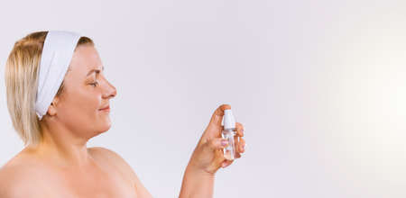Banner,long format. Caucasian senior blonde woman with headband bandage sprays a cosmetic beauty spray on a white background.