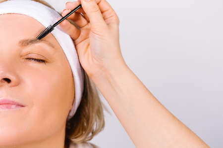 Enlarged photo where the hand of the master makes the lamination of the eyebrows of a woman with a bandage on her head. Fashion trends on a white background.