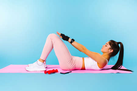 Exercise on the pink fitness mat. The brunette girl shakes the press. Blue background with return blank space.