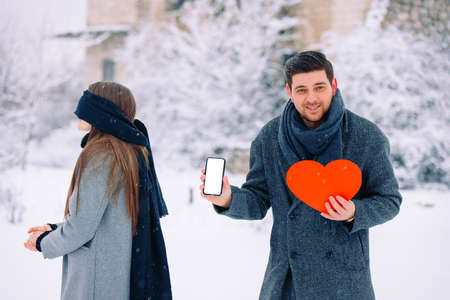 Young romantic couple, surprise outdoor, winter time. Man holding red heart and mobile phone with blank empty screen mock up copy space lookng at camera. Blind woman with closed eyes.