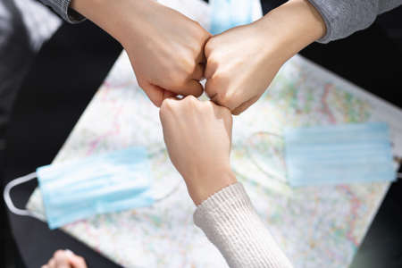 Fist bump in a pandemic tour. Searching adventures. Safe travel, photo of hands of 3 friends, above the map with protective masks. Tourism in end of quarantine. High quality photo
