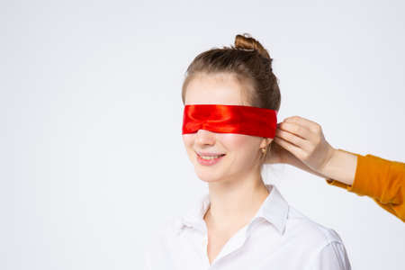 Surprised excited woman closed her eyes with red ribbon waiting for a surprise, isolated on white background with empty space. High quality photo