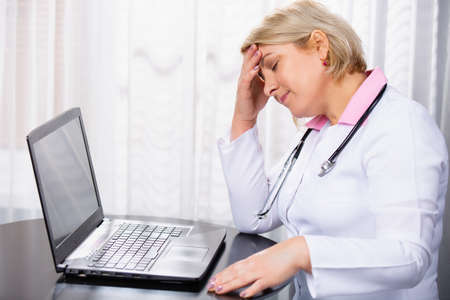 Doctor in a white coat with a stethoscope. Senior female doctor is tired. Medical worker was overworked from full graphic of online consultations, white medical office background. High quality photo Stock Photo