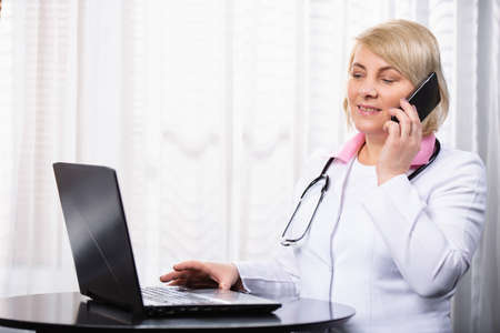 Senior female doctor in medical uniform in front of laptop with phone during online consultation, working day.