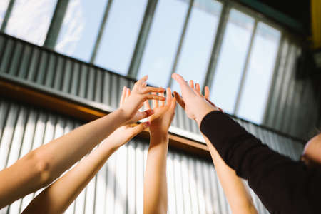Conceptual image of teamwork and cooperation with a group of people raising their hands and placing them together, Close up view of their hands. Ready for new project