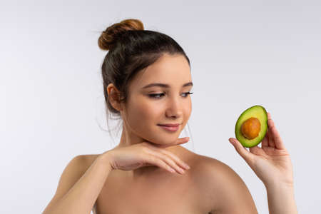 Portrait of tender young caucasian woman holding a slice of avocado, recommend healthy lifestyle or diet, Smiling female prefer natural organic product for healthy skin teeth, skincare concept
