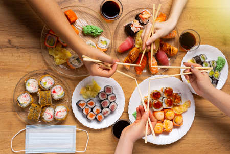 High standard sushi delivery. Asian food recommendations, family imitates sushi stick star. Sushi diner gathers friends. Japanese food concept and protective mask.