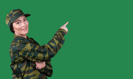A girl in a military uniform points with a forefinger to an empty space and looks at the camera with a smile. Green background and side space for text or advertisements.