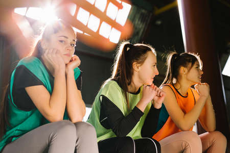 A team of young girls sitting on the bench in multi-colored vests are worried and worried about their team. The girls are ready to play. Reklamní fotografie