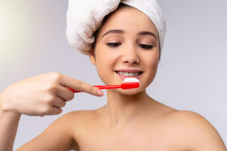 Portrait of young beautiful amazed woman with a towel on her head brushing her teeth with toothbrush