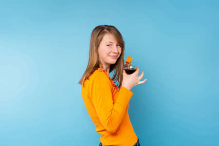 Profile portrait of girl blonde eating sushi with fresh salmon with soy sauce wearing orange sweater on blue background. High quality photo