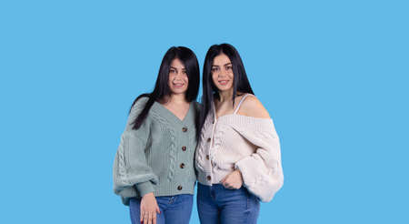 Banner in long format on a blue background with two twin sisters with long black hair, 20s, smiling and happy looking at camera. Space for information. High quality photo