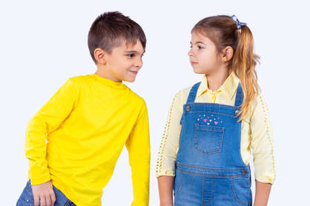 Smart good looking boy leaned over to the girl and wants to say several words to her and she is very attentive. Banque d'images
