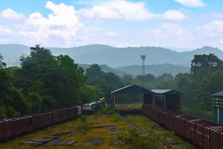 indian rail carriage waiting in its shed with a beautiful mountain in the background in Goa, India