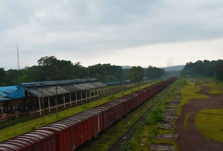 goods train waiting to leave from a station in a rainy weather