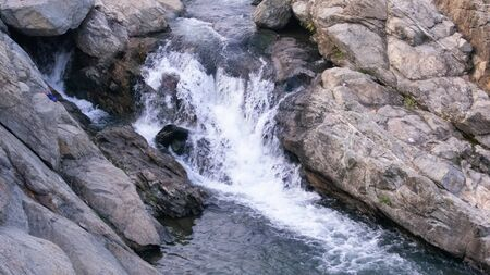 a waterfall where water is falling between the rocks