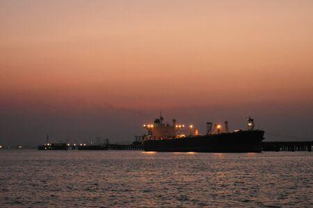 A merchant ship standing near the Port of Mumbai, captured in evening.