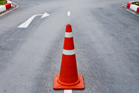 Orange traffic cone on asphalt road with white arrow to turn right ahead  photo