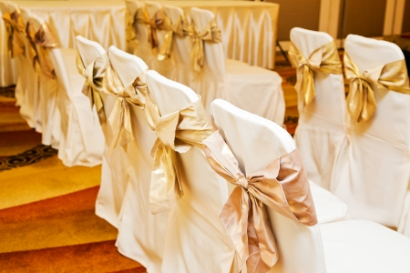 The back of yellow and gold wedding chairs photo