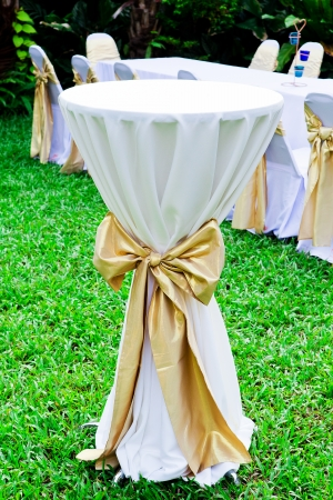 Wedding tabel in row decorated with golden color ribbon