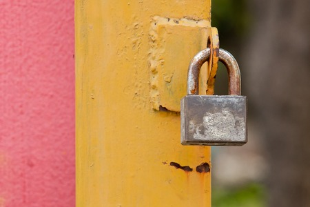 disuse: A decaying, peeling, grungy Yellow garage door with a lock Stock Photo