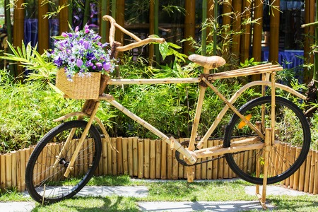 Purple flowers on a bamboo bicycle basket. Stock Photo