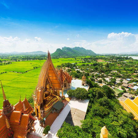 A view from the top of the pagoda, golden buddha statue with rice fields and mountain, Wat Tham Sua(Tiger Cave Temple), Tha Moung, Kanchanburi, Thailand photo