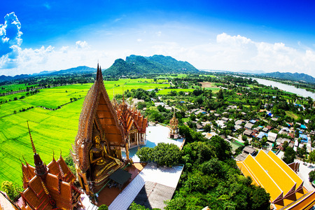Golden buddha statue with mountain, Wat Tham Sua(Tiger Cave Temple), Tha Moung, Kanchanburi, Thailand photo