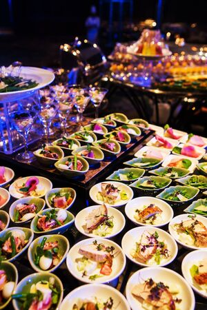 table decoration: Cocktail party with variety of desserts and food decorated in spoons arranged in orderly fashion Stock Photo