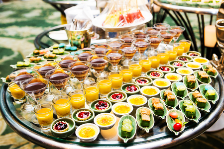 party table: Cocktail party with variety of desserts and food decorated in spoons arranged in orderly fashion Stock Photo