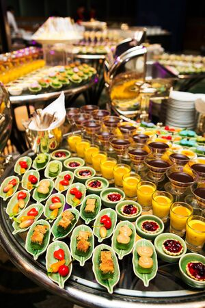 整然とした形で配置されたスプーンで装飾された様々 なデザートと料理とカクテル パーティー 写真素材