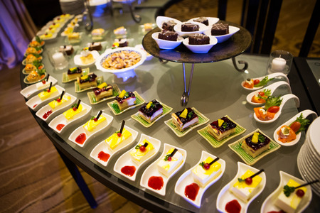 Cocktail party with variety of desserts and food decorated in spoons arranged in orderly fashion Stock Photo