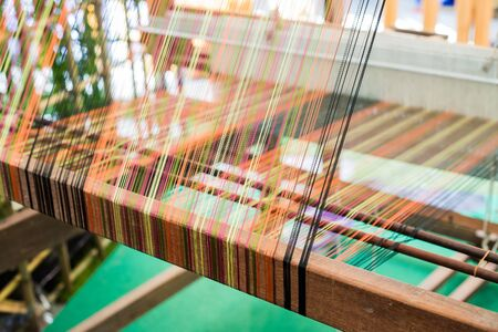 rug weaving: Detail of weaving loom for homemade silk or textile production Stock Photo