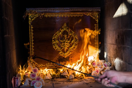 cremation: The Buddhist Thai cremation chamber and hand of undertaker Stock Photo