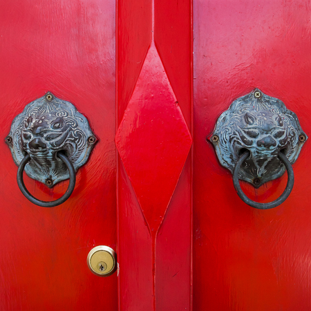 Closed Up of Vintage Chinese Lion Door Knocker on Red Wooden Doo