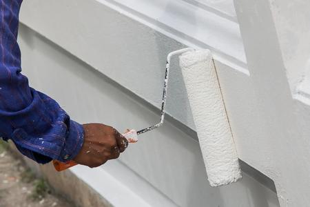 ペイント ローラーで壁を塗る白い手袋で画家の手のクローズ アップ