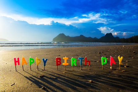 Happy birthday colorful candles on a beach.