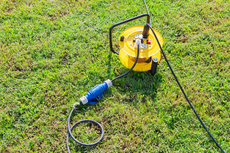 plugged in: Electrical outlet in grass with extension cord plugged in